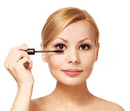 Mulher bonita que aplica o rímel em suas pestanas, isoladas Imagens de Stock