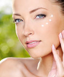 Mulher bonita que aplica os olhos próximos de creme Imagens de Stock Royalty Free