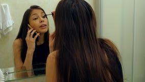 Mulher bonita que aplica a pestana do rímel na frente do espelho, ao falar através do smartphone no banheiro Foto de Stock Royalty Free