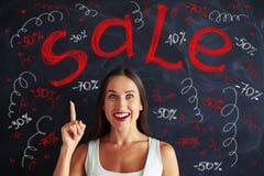 Mulher bonita que aponta acima com seu dedo na propaganda o da venda Foto de Stock