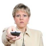 Mulher bonita que aponta o telecontrole com luz fora imagem de stock