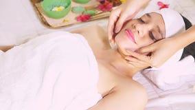 Mulher bonita que aprecia a massagem de cara video estoque