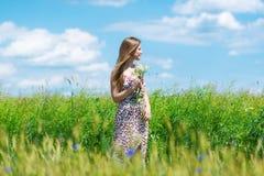 Mulher bonita que aprecia o campo da centáurea e o céu azul Imagem de Stock Royalty Free