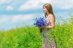 Mulher bonita que aprecia o campo da centáurea e o céu azul Fotografia de Stock