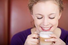 Mulher bonita que aprecia o macchiato do latte Imagem de Stock Royalty Free