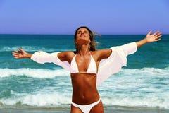 Mulher bonita que aprecia o sol na frente do oceano. Imagens de Stock