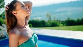 Mulher bonita que aprecia a piscina fotografia de stock