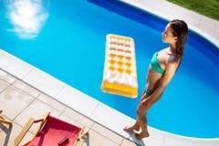 Mulher bonita que aprecia a piscina imagem de stock royalty free