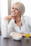 Mulher bonita que aprecia um café da manhã saudável Foto de Stock Royalty Free