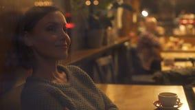 Mulher bonita que aprecia a vista da janela à rua iluminada, feriados video estoque
