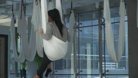Mulher bonita que balança ao sentar-se em uma rede para a ioga no estúdio dentro Menina atlética que pratica a ioga aérea vídeos de arquivo