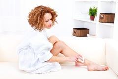 Mulher bonita que barbeia seus pés com epilator Fotografia de Stock Royalty Free
