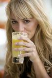 Mulher bonita que bebe um vidro do sumo de laranja Fotografia de Stock