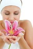 Mulher bonita que cheira uma flor Fotografia de Stock Royalty Free