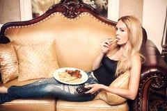 Mulher bonita que come a batata e que olha a tevê fotos de stock royalty free