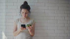 Mulher bonita que compra em linha com cartão de crédito usando o smartphone em casa vídeos de arquivo