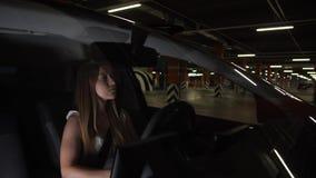 Mulher bonita que conduz o carro com o estacionamento da cidade vídeos de arquivo