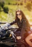 Mulher bonita que conduz uma motocicleta fotografia de stock