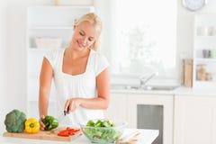 Mulher bonita que corta a pimenta Foto de Stock