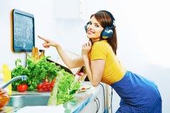A mulher bonita que cozinha na cozinha e escuta música Fotografia de Stock Royalty Free