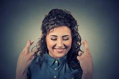 Mulher bonita que cruza seus dedos, olhos fechados Imagem de Stock Royalty Free