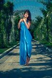 Mulher bonita que dança com os pés descalços em um vestido azul longo Imagem de Stock
