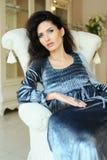 Mulher bonita que descansa em uma cadeira branca no interior luxuoso imagens de stock