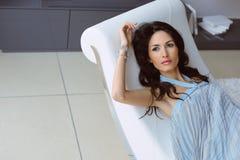 Mulher bonita que descansa na cadeira branca imagens de stock royalty free