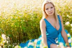 Mulher bonita que desgasta o vestido azul em um campo imagem de stock