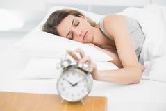 Mulher bonita que desliga o despertador com os olhos fechado Fotos de Stock Royalty Free