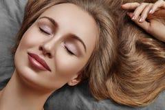 Mulher bonita que dorme ao encontrar-se na cama com conforto Sonhos doces Modelo 'sexy' com o cabelo encaracolado que relaxa em f imagem de stock