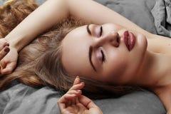Mulher bonita que dorme ao encontrar-se na cama com conforto Sonhos doces Modelo 'sexy' com o cabelo encaracolado que relaxa em f imagem de stock royalty free