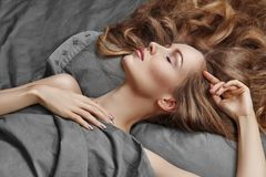 Mulher bonita que dorme ao encontrar-se na cama com conforto Sonhos doces Relaxamento modelo 'sexy' em folhas cinzentas imagens de stock