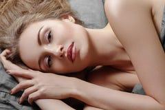 Mulher bonita que dorme ao encontrar-se na cama com conforto Sonhos doces Relaxamento modelo 'sexy' em folhas cinzentas fotografia de stock royalty free