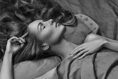 Mulher bonita que dorme ao encontrar-se na cama com conforto Sonhos doces Relaxamento modelo 'sexy' em folhas Rebecca 36 imagem de stock royalty free