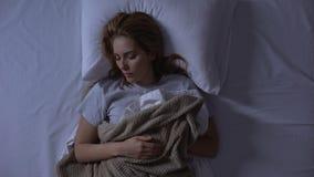Mulher bonita que dorme sadiamente em sua cama ortopédica confortável, cuidados médicos video estoque
