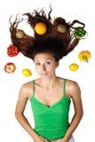 Mulher bonita que encontra-se com frutas e cabelo Fotografia de Stock