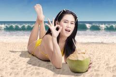 Mulher bonita que encontra-se com gesto aprovado Foto de Stock
