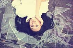 Mulher bonita que encontra-se em glas quebrados Fotografia de Stock Royalty Free