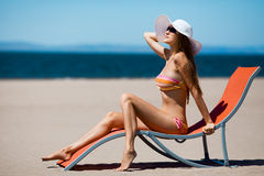Mulher bonita que encontra-se em um deckchair na praia Fotografia de Stock Royalty Free