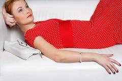 A mulher bonita que encontra-se em um sofá fotografia de stock royalty free