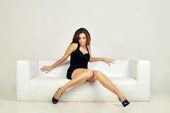 Mulher bonita que encontra-se em um sofá branco, sobre fotos de stock royalty free