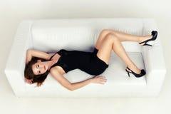 Mulher bonita que encontra-se em um sofá branco, sobre imagens de stock