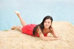 Mulher bonita que encontra-se em uma areia perto de uma praia Foto de Stock