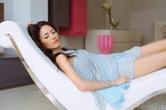 Mulher bonita que encontra-se em uma cadeira no vestido azul Fotografia de Stock Royalty Free