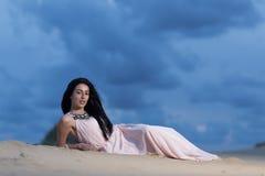 Mulher bonita que encontra-se em uma duna de areia Foto de Stock Royalty Free