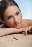 Mulher bonita que encontra-se na areia que começ o prazer foto de stock royalty free