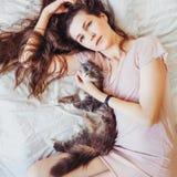 Mulher bonita que encontra-se na cama com seu gato encantador imagem de stock royalty free