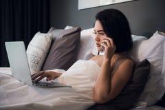 Mulher bonita que encontra-se na cama e que faz um telefonema Moça que usa seu portátil em casa Mulher bonita que relaxa em imagens de stock