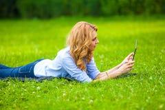 Mulher bonita que encontra-se na grama com tabuleta Fotos de Stock Royalty Free
